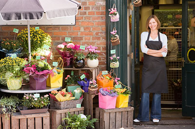 Woman standing in front of her small business flower shop.  10 Step Guide to Starting a Small Business.  The Miller Insurance Agency Everett Washington