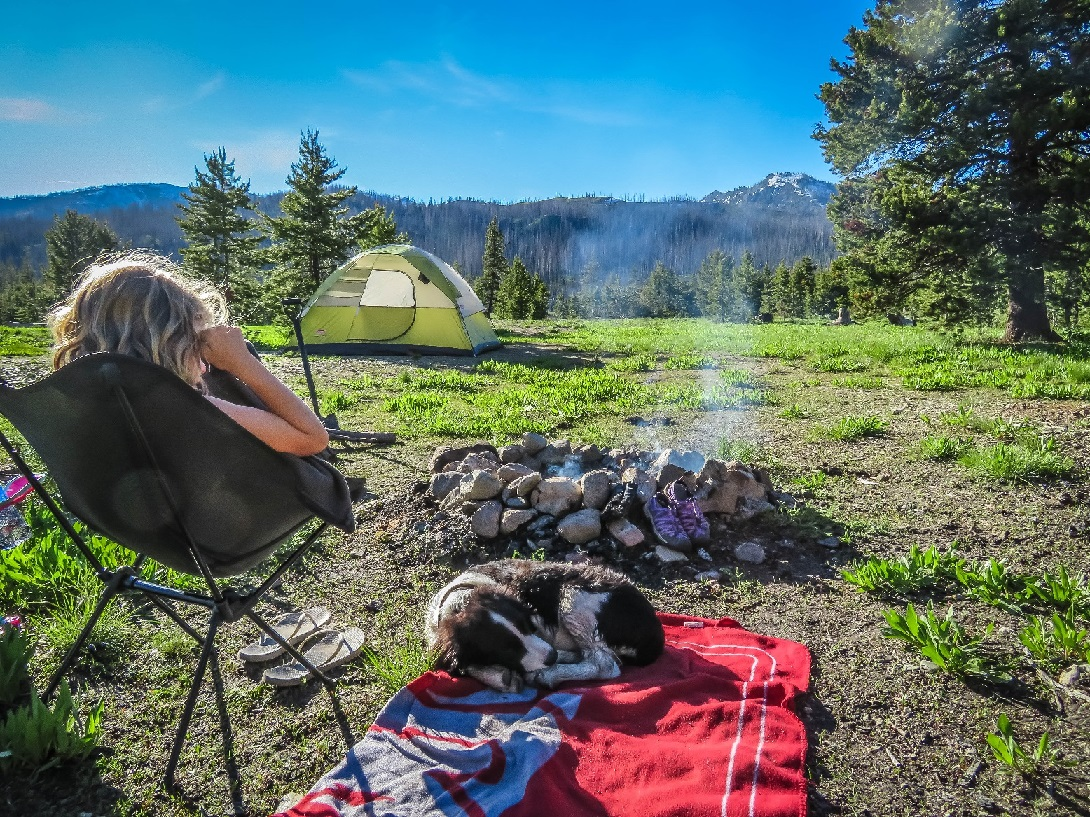 Child and dog sitting around campfire in the mountains.  Protecting your camp gear.  Home Insurance Coverage - The Miller Insurance Agency Everett Washington